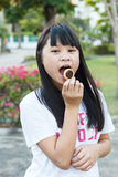 Thai girl eating chocolate cookie. Royalty Free Stock Image