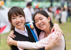 Thai girl is hugging her friend who graduated a master degree. Thai girl is hugging her friend with university gown who graduated a master degree stock photography