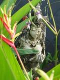 Thai God in Garden. Focus on god through flowers Stock Image
