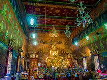 Thai golden Buddha statue in temple with mural painting. Royalty Free Stock Photography