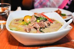 The Thai green curry beef in big white bowl at restaurant table. Thai green curry beef in big white bowl at restaurant table royalty free stock image