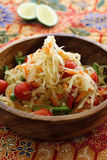 Thai green papaya salad. Served in a wood bowl on a piece of batik print fabric Royalty Free Stock Images