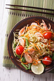 Thai green papaya salad with shrimp close-up. vertical top view. Thai green papaya salad with shrimp close-up on a plate on the table. vertical top view royalty free stock images