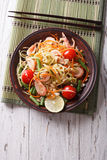 Thai green papaya salad with shrimp. vertical top view. Thai green papaya salad with shrimp on a plate on the table. vertical top view stock photos