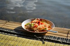 Thai Green Papaya Salad SOM TAM in bamboo hut over. Green Papaya Salad SOM TAM is a popular dish in Thailand, Laos and Cambodia. The dish is made with unripe stock images