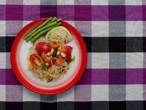 Thai green papaya salad Som tam in traditional floral print tray on purple Thai loincloth background. Thai green papaya salad, Som Tam, famous street food of stock photography