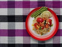 Thai green papaya salad Som tam in traditional floral print tray on purple Thai loincloth background. Thai green papaya salad, Som Tam, famous street food of royalty free stock photography