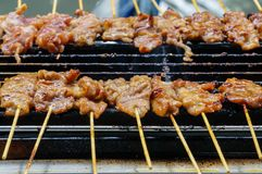 Thai grilled pork. The pork is marinated in tangy fish sauce and cilantro and brushed with rich, creamy coconut milk while being grilled over hot coals Stock Photos