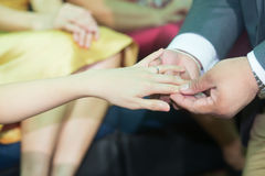 Thai groom putting a wedding ring Stock Images
