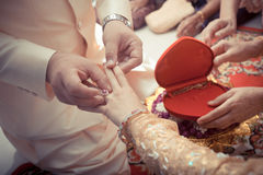 Thai groom putting a wedding ring Royalty Free Stock Photo