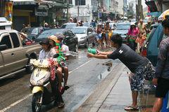 Thai guy throws water to girls on a bike Stock Photography