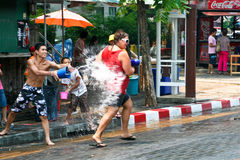 Thai guy throws water at tourist on Royalty Free Stock Photography