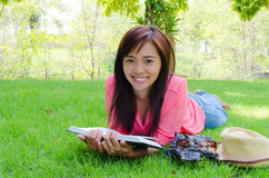 Thai happy woman reading book in park. Thai happy woman lie on ground and reading book in park Royalty Free Stock Image