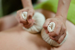 Thai herbal hot pack massage. On woman body in the spa salon. Beauty treatment concept royalty free stock photo