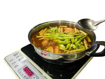Thai hot and sour soup, hot pot, serve with assorted vegetables. Thai hot and sour soup, hot pot, serve with assorted vegetables, on induction cooker royalty free stock images