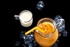 Thai ice tea in glass jar with milk and ice on black background Stock Photos