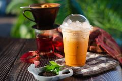 Thai Iced tea in a glass. And Tea dust on the wood surface stock images