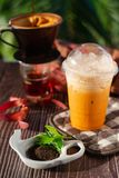 Thai Iced tea in a glass. And Tea dust on the wood surface royalty free stock image