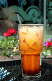 Thai Iced Tea in Tall Glass. Refreshing thirst quencher of iced tea with cream in tall glass and straw Stock Images