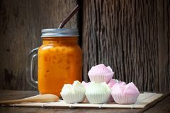 Thai Iced Tea with Thai Rice Flour Muffins `Kanom Tuay Fu`. On wood background Stock Image