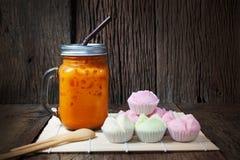 Thai Iced Tea with Thai Rice Flour Muffins Kanom Tui Fu. On wood background Royalty Free Stock Photography