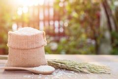 Thai jasmine rice in small sack on wooden table with sunlight Stock Photo