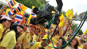 Thai King's 85th Birthday. Thai royalists celebrate the 85th birthday of Thai King Bhumibol Adulyadej in front of a remote television camera while attending Royalty Free Stock Images