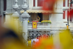 Thai King's 85th Birthday. Thailand's King Bhumibol Adulyadej, framed by waving Thai and royal flags, makes a rare public appearance at the balcony of the Royalty Free Stock Image