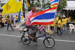 Thai King's 85th Birthday. A Thai man rides a bicycle decorated with Thai and royal flags on while attending celebrations of the 85th birthday of Thai King Royalty Free Stock Photo