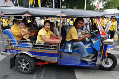 Thai King's 85th Birthday. Thai royalists ride a tuk-tuk taxi after attending celebrations of the 85th birthday of Thai King Bhumibol Adulyadej on the Royal Royalty Free Stock Photography