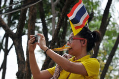 Thai King's 85th Birthday. A Thai royalist uses a smratphone to photograph the celebrations on the Royal Plaza on the occasion of the Thai King Bhumibol Royalty Free Stock Photo