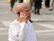 Thai King's 85th Birthday. A Thai Buddhist nun talks on a mobile phone while attending the celebrations on the Royal Plaza on the occasion of the Thai King Stock Images