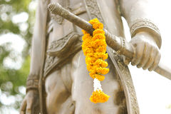 Thai king statue with marigold on sword Royalty Free Stock Images