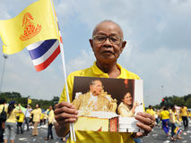 Thai Kings 85th Birthday. A Thai man holds a portrait of Thai King Bhumibol Adulyadej after attending celebrations of the Kings 85th birthday held on the Royal Stock Photos