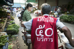 Thai labour No.50. MAE SOT, THAILAND - OCT24 : Tricycle bicycle taxi include shirt big print RANG GNAN THAI 50 ( Thai labour No.50)  taking passenger out fresh Royalty Free Stock Photo