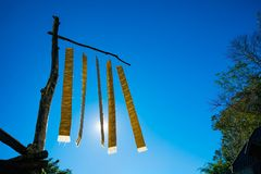 Pillar of thai lanna flag on blue sky background. Thai lanna flag hanging on pillar wood Royalty Free Stock Images