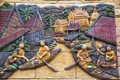 Thai lifestyle stone carving on the wall. Offerings in a monk`s alms bowl in long wooden boats  at at Wat Tai Phra Chao Yai Ong Tue,Ubonratchathani Province Royalty Free Stock Image