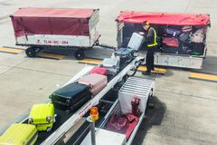 Thai Lion Air ground staff load passenger luggages on the airplane through the conveyor. CHIANG MAI, THAILAND - 28 June 2018 - Thai Lion Air ground staff load stock images