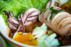 Thai local food: seafood spicy noodles with squid, boiled egg and meat ball. Stock Image