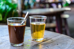 Thai local hot coffee with hot tea on wooden table.  Royalty Free Stock Image