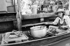 Thai locals sell food and souvenirs at famous Damnoen Saduak floating market, Thailand Stock Photo