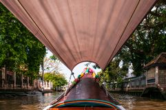 Thai long tail boat with garlands in Bangkok canal Klong, famo. Thai long tail boat with garlands in Bangkok`s canal Klong, famous river and canal transportation royalty free stock photography