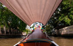 Thai long tail boat with garlands in Bangkok canal Klong, famo. Thai long tail boat with garlands in Bangkok`s canal Klong, famous river and canal transportation royalty free stock photos