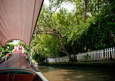 Thai long tail boat with garlands in Bangkok canal Klong, famo. Thai long tail boat with garlands in Bangkok`s canal Klong, famous river and canal transportation royalty free stock image