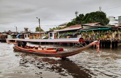 Thai long tail boat with garlands in Banhkok canal Klong, famo. JUL 10, 2018 Bangkok, Thailand - Thai long tail boat with garlands in Banhkok`s canal stock image