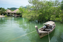 Thai long tail boat with mangrove and huts view Royalty Free Stock Photography