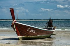 Thai Longboat beached on the sea. Cloudy sky mountains in the background royalty free stock photography