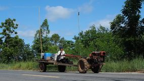 A Thai man drives a long-handled two-wheel tractor stock footage