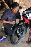Thai man repairing a motorcycle Stock Photography
