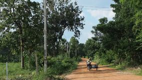 A Thai man rides a motorcycle sidecar on dirt road stock video footage